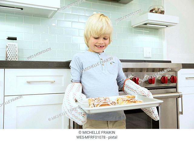 Smiling boy holding baking tray with cinammon buns