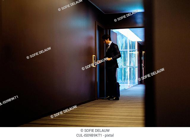 Businessman with wheeled luggage entering hotel bedroom