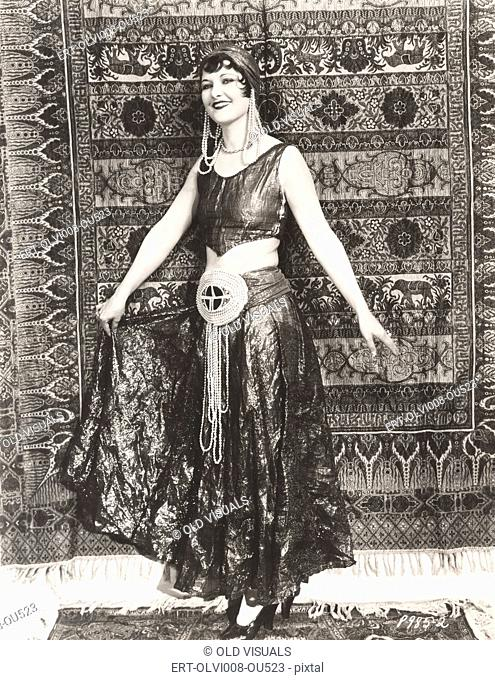 Woman dressed in gypsy costume standing in front of rug