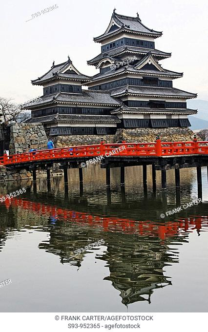 A view of Matsumoto castle showing the moat, some stone work around it, and a red wooden bridge, Nagano, Japan