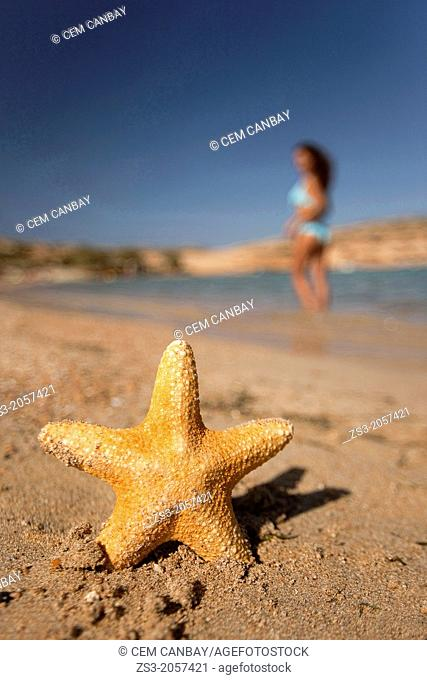 Starfish and a woman in bikini on the beach, Naxos, Cyclades Islands, Greek Islands, Greece, Greece, Europe