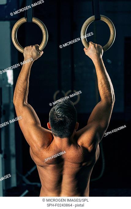 Man exercising on gymnastic rings