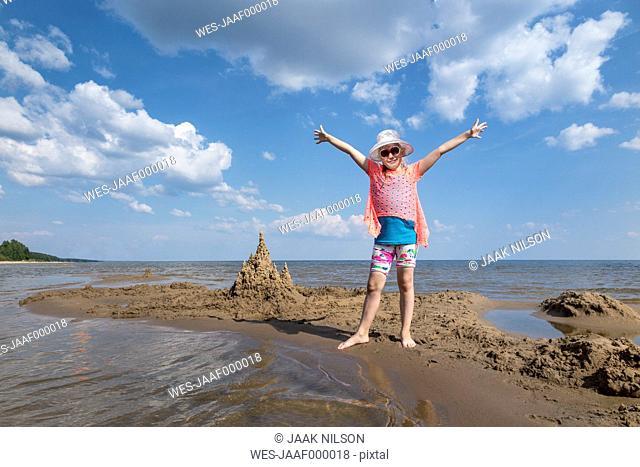 Estonia, Lake Peipus, girl on beach with raised arms