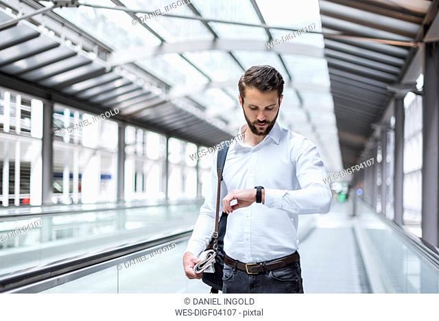 Young businessman on moving walkway checking the time