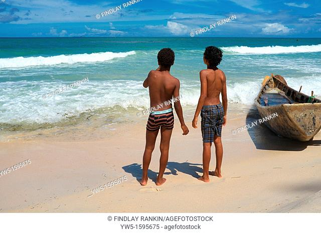 Two young boys standing on the beach at Beau Vallon next to a traditional styled fishing boat, Mahe, Seychelles