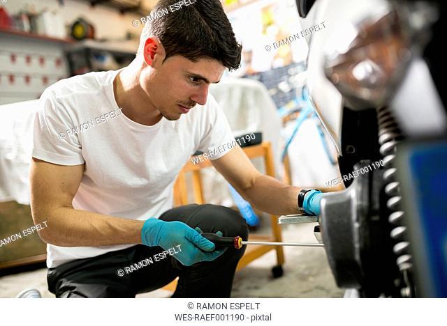 Young mechanic repairing motor scooter in garage