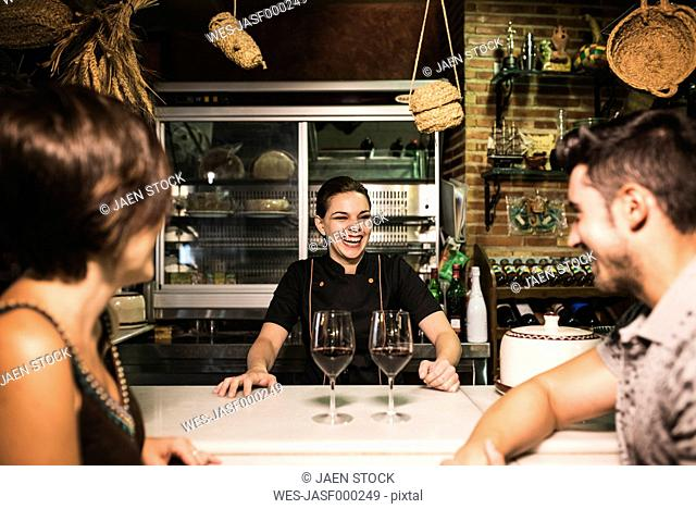 Laughing waitress and couple at bar with red wine glasses