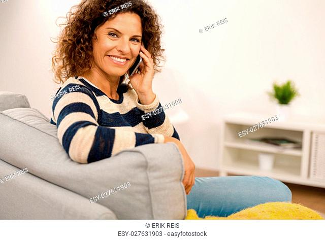 Top view of a beautiful woman on the sofa sending a text message