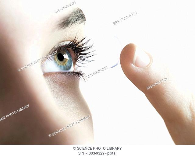 Contact lens use. Woman putting in a contact lens