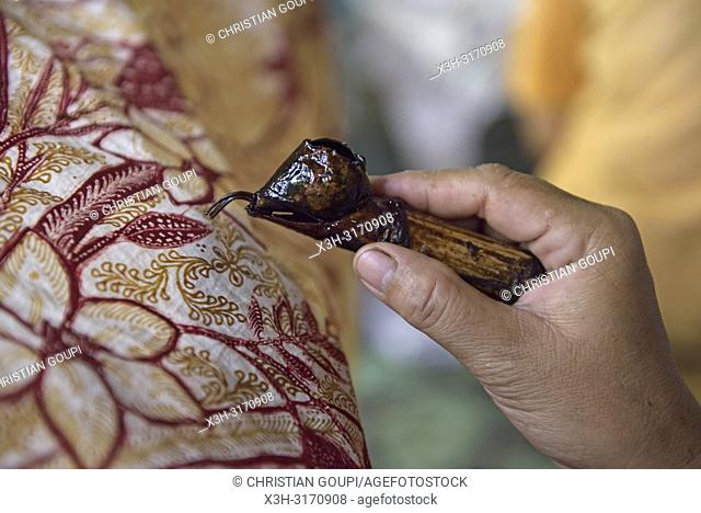 woman using a pen-like tool, called ''canting'', to apply liquid hot wax to create pattern on the fabric before dyeing, workshop of Kidang Mas Batik House