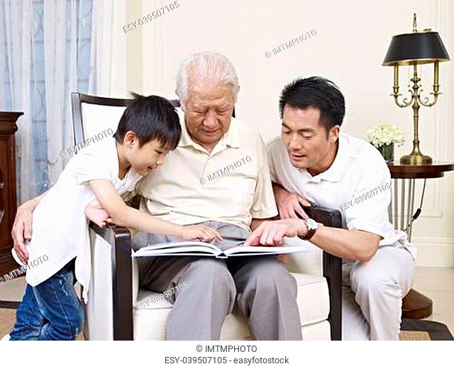 asian son, father and grandfather reading a book together