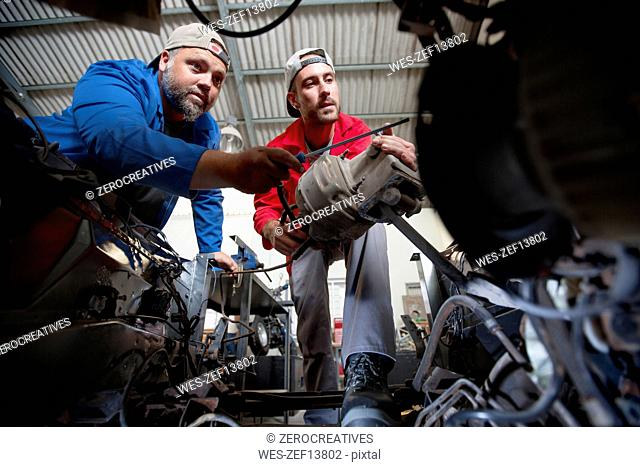 Mechanics repairing car in workshop