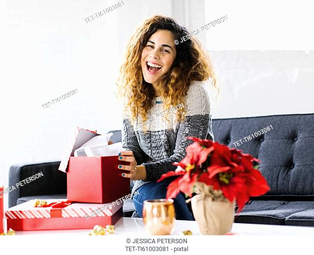 Happy woman on sofa opening Christmas gift