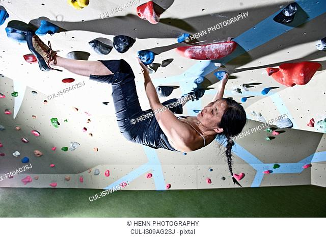 Mature woman bouldering upside down on climbing wall