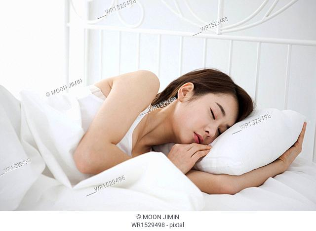 a woman sleeping in bed with white sheets