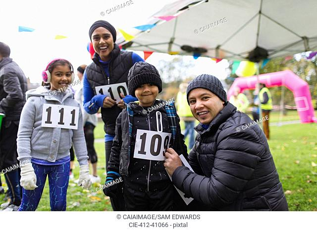 Portrait smiling family preparing for charity run in park