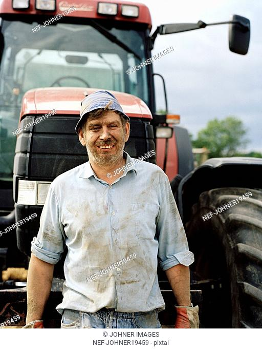 A happy farmer in front of a tractor