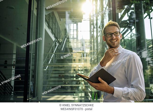 Smiling businessman holding notebook in lobby