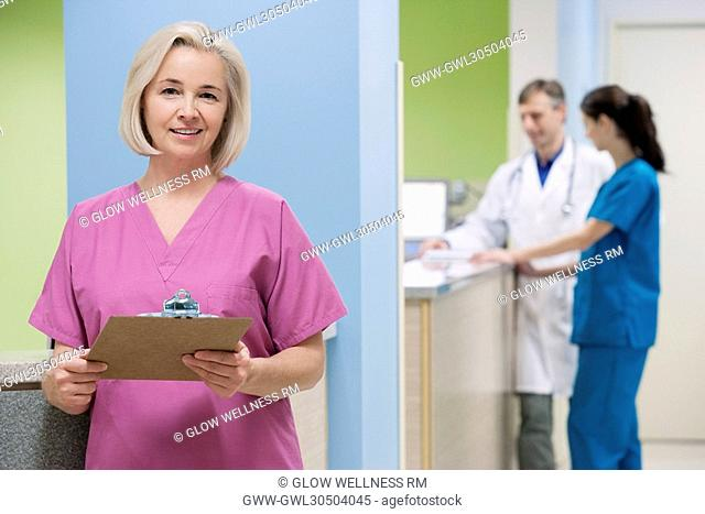Female nurse holding a clipboard with a doctor and a nurse in the background