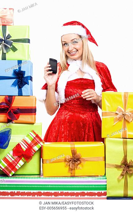 Happy woman in Christmas costume with phone and many presents, isolated on white background