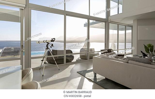 Sunny, tranquil modern luxury home showcase interior living room with telescope and ocean view