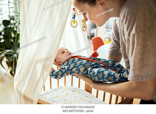 Mother putting her newborn baby boy into crib