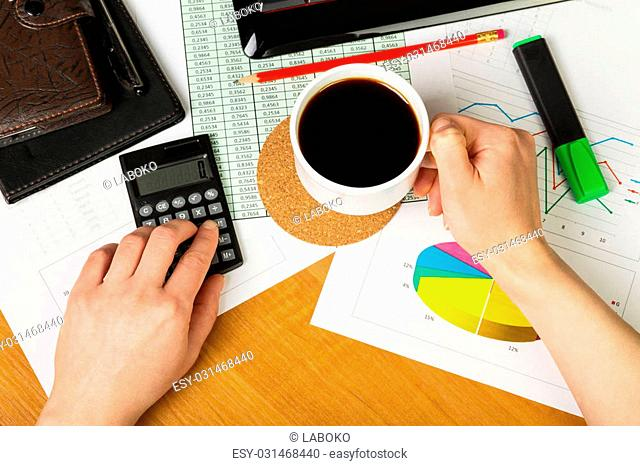 Calculator and cup of coffee in hand on the background of the desktop, view from above