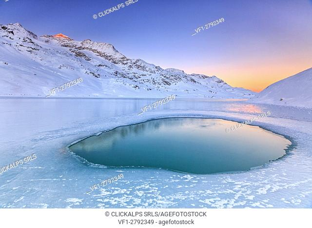 Soft colors of a cold dawn reflected in a pool of turquoise water surrounded by the snow in the middle of White Lake. Bernina Pass
