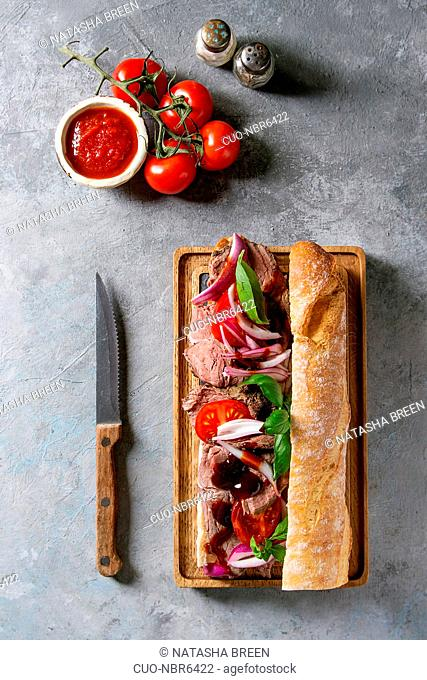 Beef baguette sandwich with tomatoes, basil, red onion served on wooden serving board with ingredients above over grey texture background