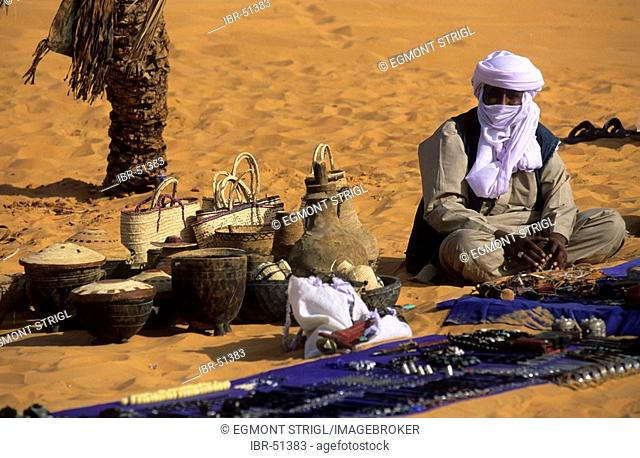 Touareg sitting in the sand selling souvenirs, Libya