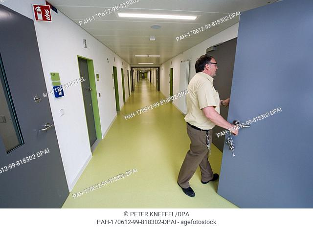 A judicial officer opens the door to a prison cell at the new Deportation Detention Centre in Eichstaett, Germany, 12 June 2017