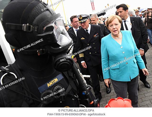 15 June 2019, Mecklenburg-Western Pomerania, Stralsund: Chancellor Angela Merkel (CDU) walks past a soldier in a diving suit