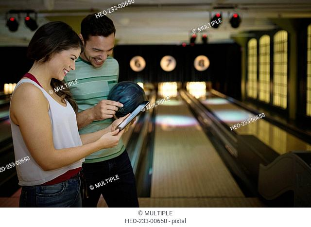 Young couple using digital tablet at bowling alley