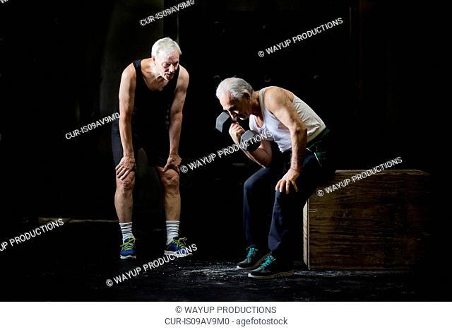 Senior men training with dumbbell in dark gym