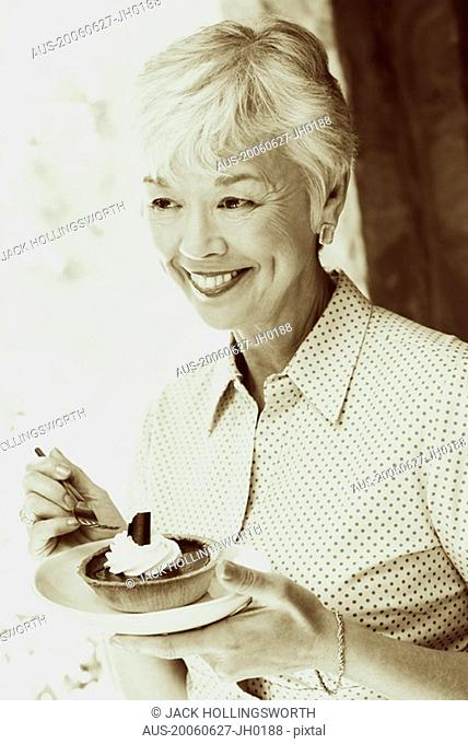 Close-up of a senior woman eating a tart with a fork