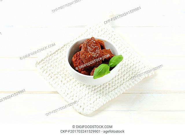 bowl of dried and pickled tomatoes on white table mat