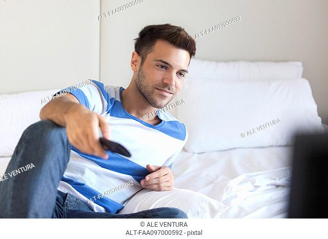 Young man reclining on bed watching tv