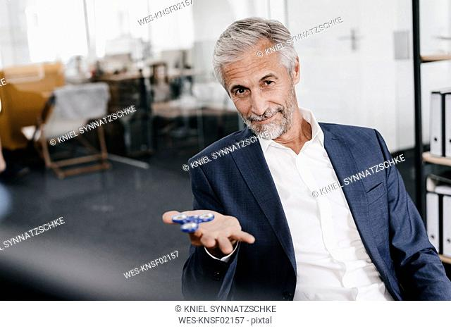 Portrait of mature businessman in office with fidget spinner