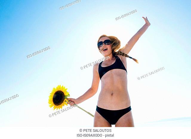 Portrait of teenage girl wearing bikini, holding sunflower, arm raised