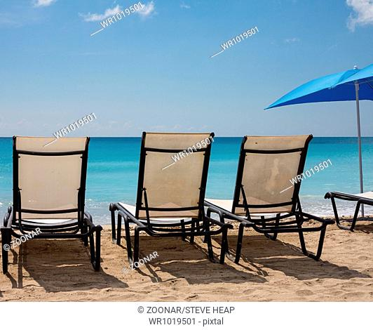 Three beach loungers and umbrella on sand