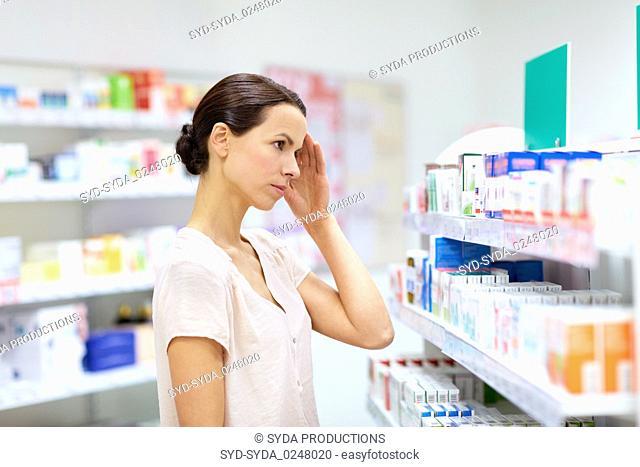 customer with headache choosing drugs at pharmacy