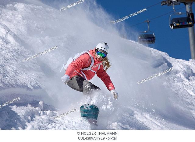 Young woman snowboarding on steep mountain, Hintertux, Tyrol, Austria