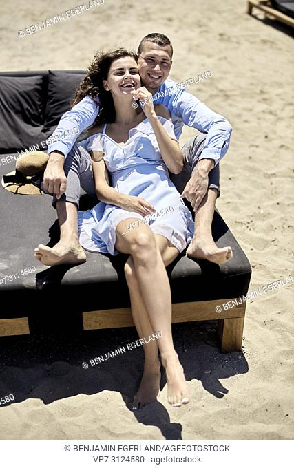 couple sitting on sunbeds at beach, vacations, summer, love
