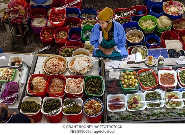 A Woman Sells Pickled Vegetables From A Stall In The Chorsu Bazaar, Tashkent, Uzbekistan