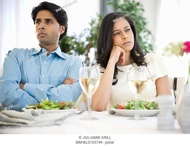 Unhappy mixed race couple dining together