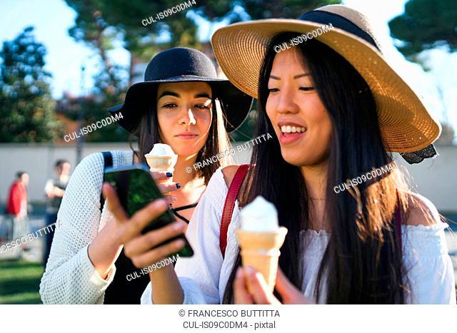 Friends with ice cream cones, using smartphone