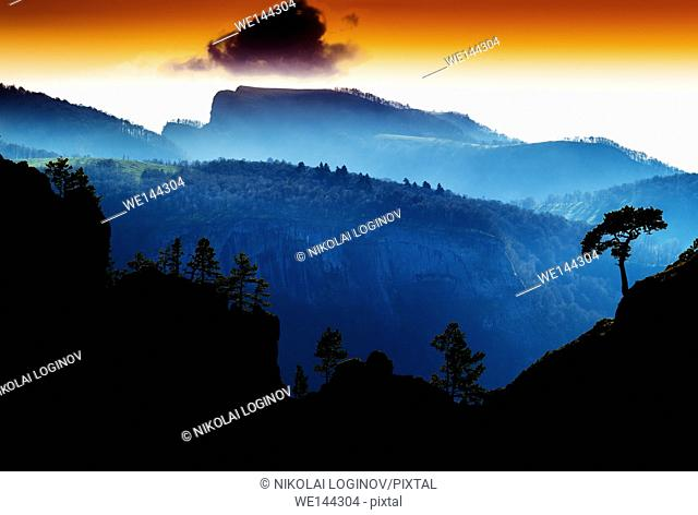 Horizontal vdramatic mountain trees on rocks silhouette sunset background backdrop