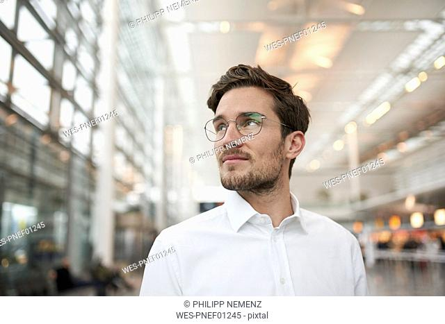 Portrait of young businessman wearing glasses looking around