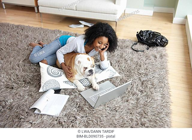 Black woman laying on floor with laptop and dog