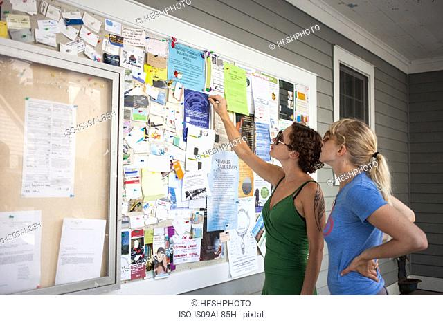 Two mid adult women looking up at community notice board